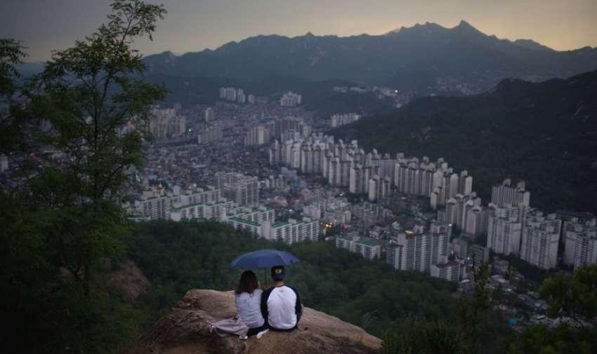 En una foto tomada el 11 de junio 2015 un refugio pareja debajo de un paraguas mientras se sientan en una colina con vistas al horizonte de la ciudad más septentrional de Seúl , mirando al norte. AFP