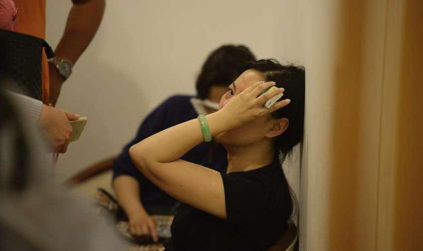 Una mujer llora por la desaparición de sus familiares a las puertas de una agencia de viajes que participó en la organización del crucero por el río Yangtsé en Shangai (China) hoy, martes 2 de junio de 2015. EFE