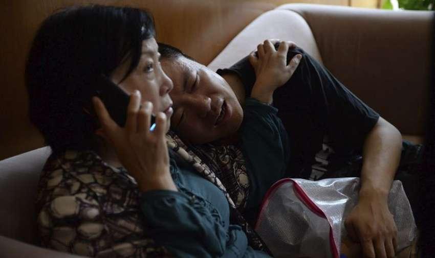 Un hombre acompañado de su tía llora por la desaparición de sus familiares a las puertas de una agencia de viajes que participó en la organización del crucero por el río Yangtsé en Shangai (China) hoy, martes 2 de junio de 2015. EFE