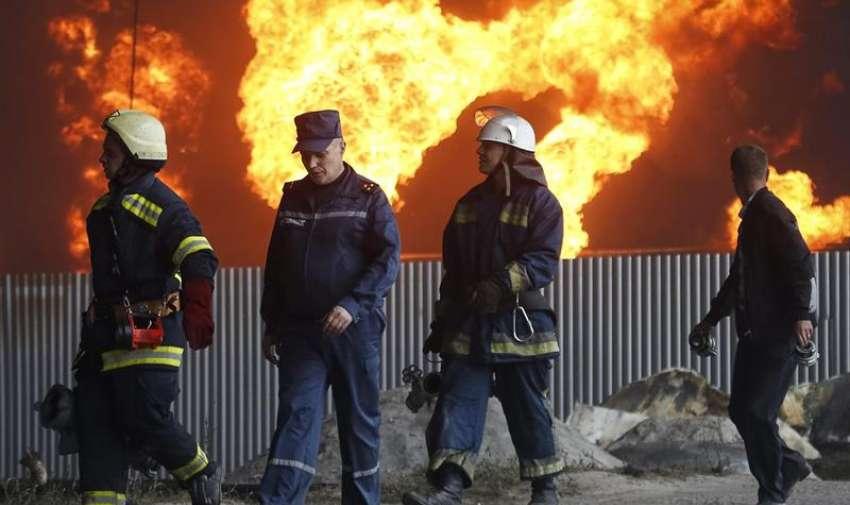 Varios bomberos trabajan en las labores de extinción del incendio declarado en un depósito de combustible cerca de la localidad de Vasylkiv, a las afueras de Kiev, Ucrania, el 9 de junio del 2015. EFE