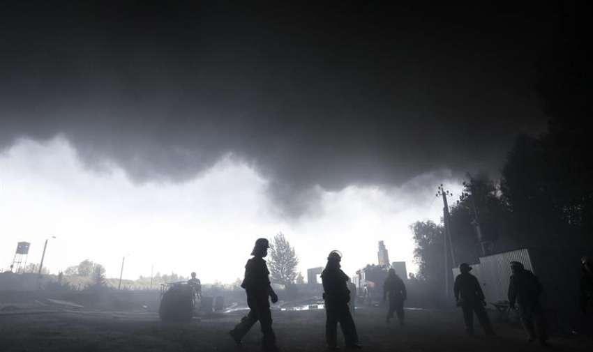 Varios bomberos trabajan en las labores de extinción del incendio declarado en un depósito de combustible cerca de la localidad de Vasylkiv, a las afueras de Kiev (Ucrania) hoy, martes 9 de junio de 2015. EFE