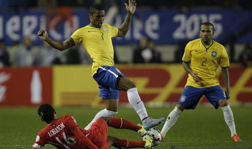 El centrocampista brasileño Douglas Costa (c) lucha el balón con el centrocampista peruano Carlos Augusto Lobatón (i), durante el partido Brasil-Perú, del Grupo C de la Copa América de Chile 2015. EFE