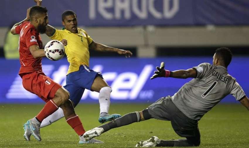 El centrocampista brasileño Douglas Costa (c) dispara a puerta entre el centrocampista peruano Josepmir Aarón Ballón (i) y el portero Quiroz Gallese (d), durante el partido Brasil-Perú, del Grupo C de la Copa América de Chile 2015, en el Estadio Municipal Bicentenario Germán Becker de Temuco, Chile. EFE