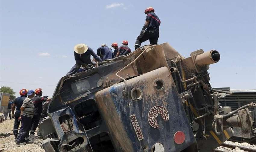 Miembros de los servicios de rescate buscan víctimas entre los restos del tren que colisionó hoy con un camión en la localidad de El Fahes, en la región de Zaghuan, a unos 60 kilómetros al sur de la capital, hoy martes 16 de junio de 2015. EFE