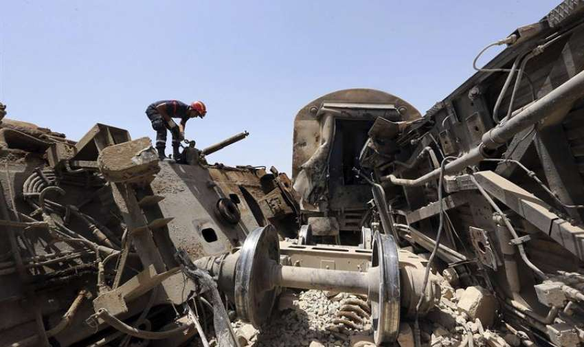 Un miembro de los servicios de rescate busca víctimas entre los restos del tren que colisionó hoy con un camión en la localidad de El Fahes, en la región de Zaghuan, a unos 60 kilómetros al sur de la capital, hoy martes 16 de junio de 2015. EFE