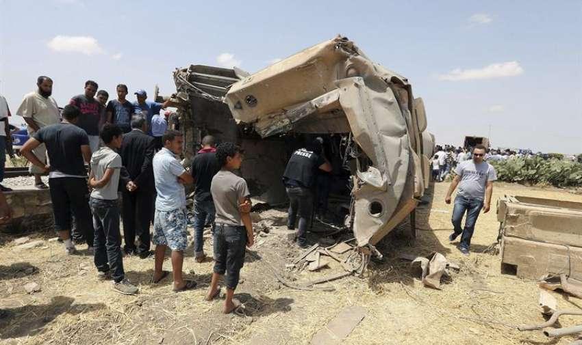 Varias personas observan los restos del tren que colisionó hoy con un camión en la localidad de El Fahes, en la región de Zaghuan, a unos 60 kilómetros al sur de la capital, hoy martes 16 de junio de 2015.  EFE
