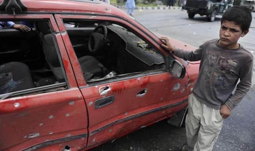 Un niño permanece junto a un vehículo dañado en el ataque contra el Parlamento en Kabul (Afganistán). EFE