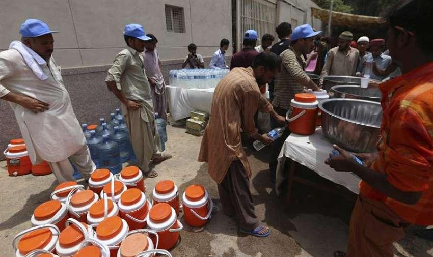 Una organizacion de ayuda distribuye agua entre la población en una calle de Karachi (Pakistán). EFE