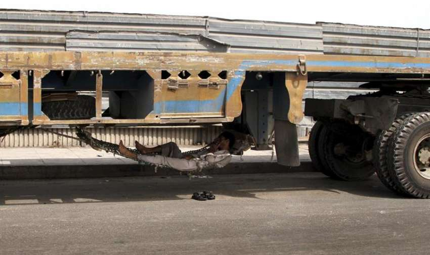 Un hombre descansa a la sombra bajo un camión Karachi (Pakistán) . EFE