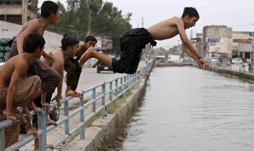 Jóvenes se refrescan en un río en Peshawar (Pakistán) hoy, miércoles 24 de junio de 2015. EFE