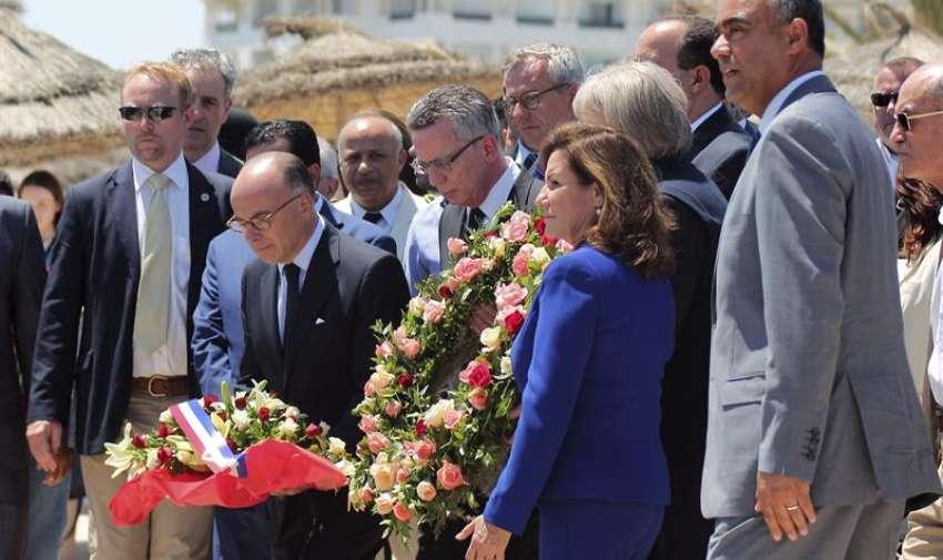 El ministro francés de Interior, Bernard Cazneuve (2, izda), y su homólogo alemán, Thomas de Maizière (centro), particpan en una ofrenda floral en la playa donde se produjo el atentado terrorista el pasado viernes junto al Hotel Imperial Marhaba en Túnez (Túnez). EFE
