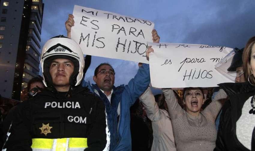 Protestas de opocitores del gobierno a las afueras de la sede de Alianza Paiz, En los exteriores de la cede de Pais simpatizantes del Gobierno y del Presidente Ecuatoriano Rafael Correa resguardan el Edificio. En la foto opocitores de gobierno destruyen una bandera de Alianza pais. API