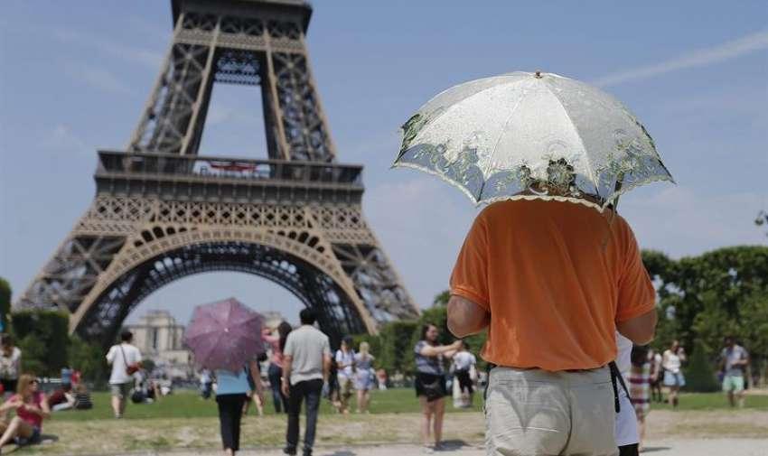 Varios turistas se protegen con sombrillas del calor, frente a la Torre Eiffel de París, Francia. EFE