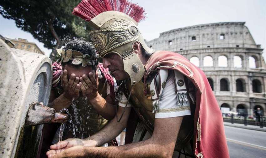 Dos hombres disfrazados de romanos beben agua de una fuente frente al Coliseo de Roma, Italia, hoy, viernes 3 de julio de 2015. EFE