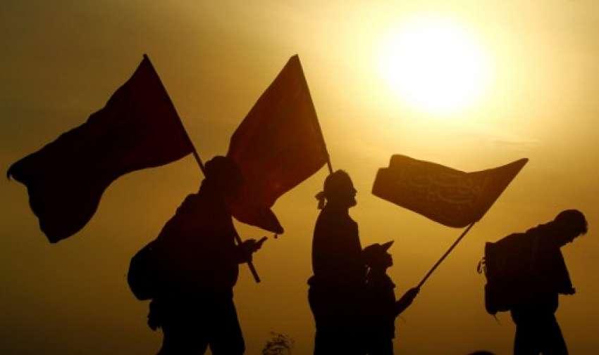 Peregrinos musulmanes llevan banderas al llegar a la entrada de la ciudad iraquí central de Karbala, a 120 kilómetros al sur de la capital Bagdad.