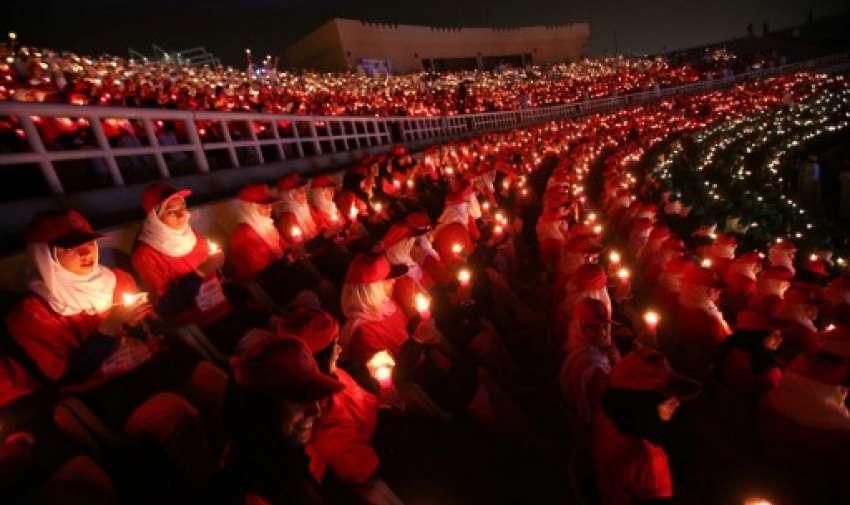 Los participantes mantienen velas formando la forma y los colores de la bandera de Omán mientras intentan romper el récord mundial Guinness de la bandera humana más grande encendida con velas.