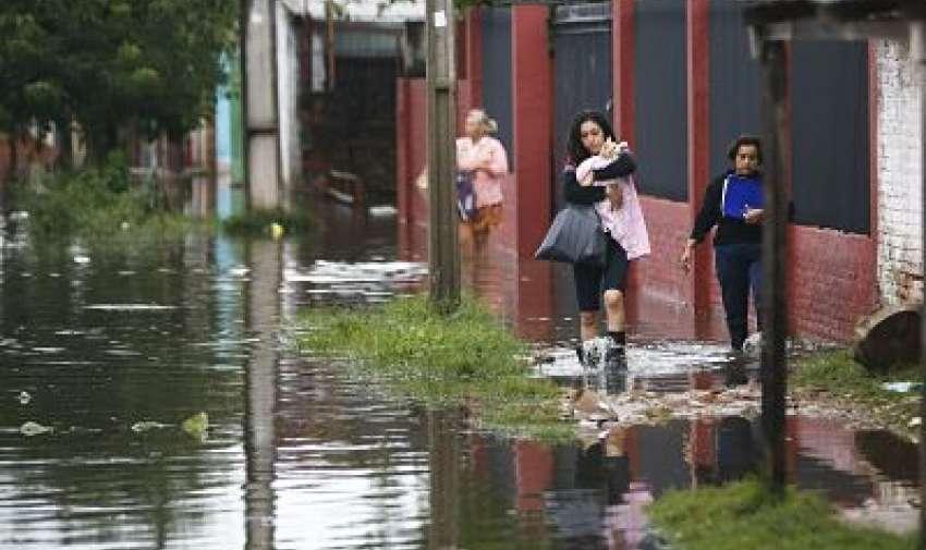Una mujer, sosteniendo a su gato, se dirige a un lugar más alto mientras camina por una calle inundada en el barrio de Santa Ana