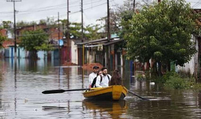 Residentes se movilizan en bote por una calle inundada en el barrio de Villa Colorada, en Asunción, Paraguay