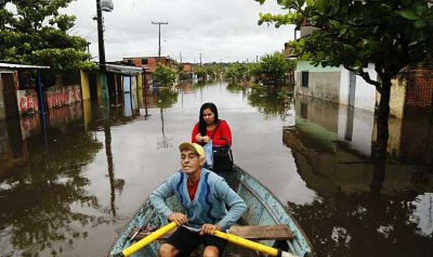 Con su hija como pasajera, Ramón Gómez, de 65 años, cruza con un bote una calle inundada en el barrio de Santa Rosa de Lima
