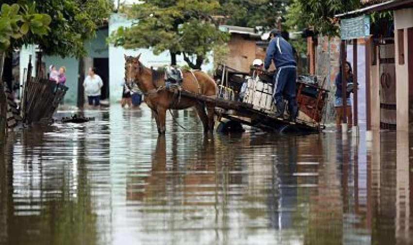 Personas que se dirigen a terrenos más altos cargan un carro de caballos en una calle inundada del vecindario Villa Colorada