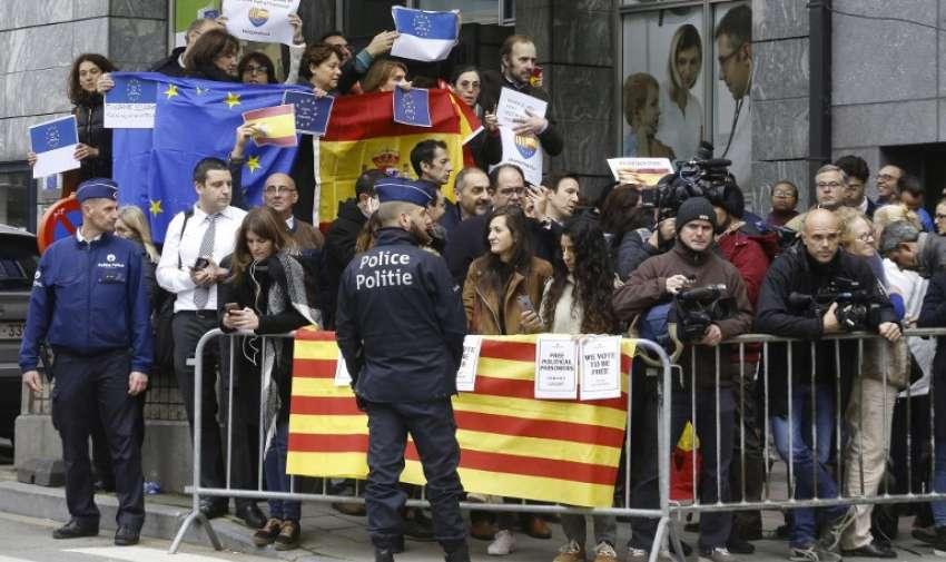 La policía se para frente a personas con banderas catalanas, españolas y europeas durante una demostración de independencia. Foto: AFP