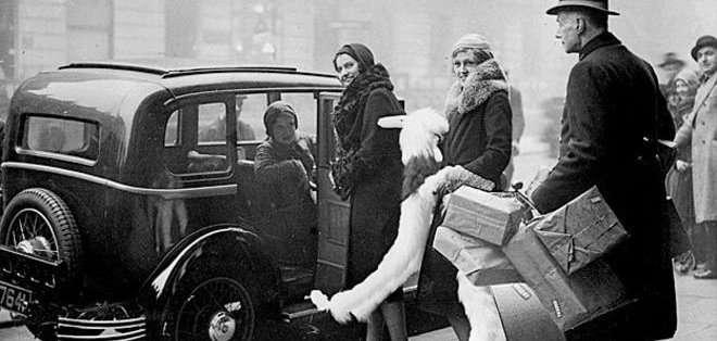 La experiencia de ir de compras ha cambiado bastante desde que estas clientas fueron acompañadas hasta el taxi por un dependiente de los almacenes Whiteleys.