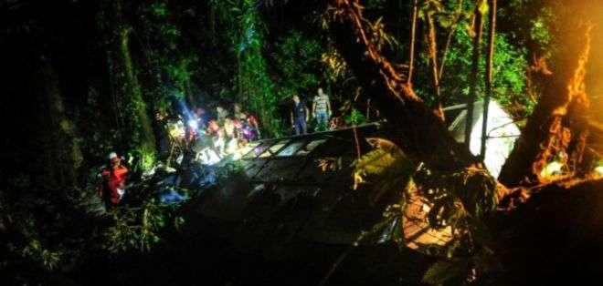 BRASIL.- Entre los hierros retorcidos del vehículo que quedaron en medio de una espesa vegetación, los bomberos sacaban a las víctimas del accidente. Fotos: AFP