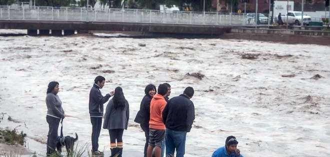 CHILE. Varias personas debieron subirse a cerros o a los techos de sus casas para evitar ser arrastradas por las aguas, en una situación descrita como similar a la de un tsunami por pobladores. Fotos: AFP