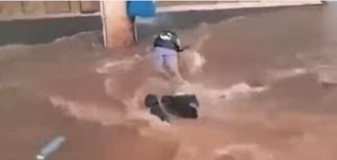 Un motociclista que se desplazaba por las calles de Brasil casi es tragado por una alcantarilla, la fuerza del agua le hace caer de su moto y tumba el vehículo.