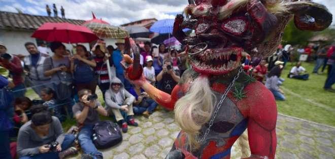 24 diablo desfilan con máscaras, billetes y revistas pornográficas tratando de tentar a los fieles. Fotos: AFP
