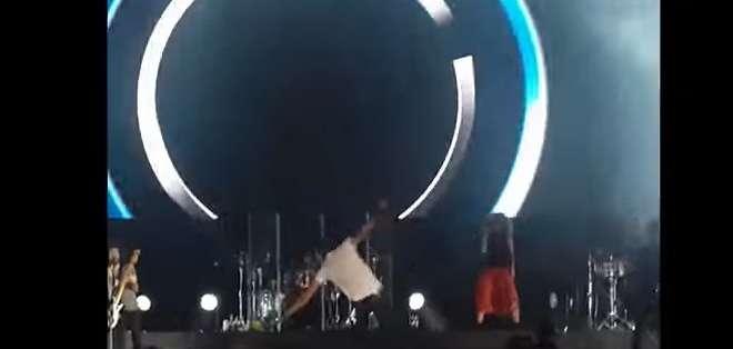 En el video se puede ver al cantautor, que está de espaldas al público, resbalar y caer.
