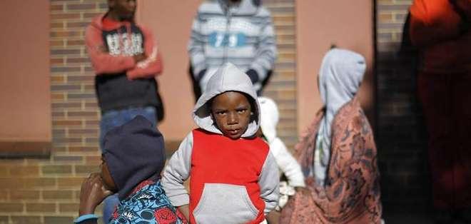 Refugiados procedentes de Mozambique y Zimbaue se sientan juntos en una comisaría, en Johannesburgo. Foto: EFE.