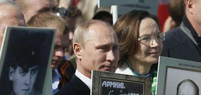 RUSIA.- Durante el acto Putin sujetaba un retrato de su padre Vladimir, quien combatió en ese conflicto. Fotos: EFE