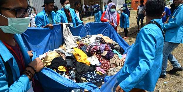 Estudiantes voluntarios de Indonesia llevan ropa donada por la población local para los migrantes.