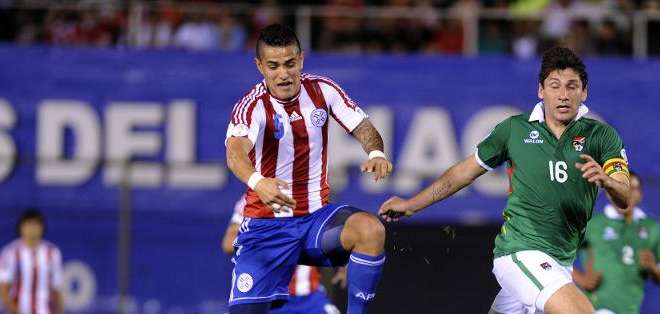 El paraguayo Víctor Ayala (C) corre junto al boliviano Ronald Raldes (D) ante la salida del portero boliviano Sergio Galarza (en el piso) en partido de las eliminatorias sudamericanas para el Mundial de Brasil-2014 jugado en el estadio Defensores del Chaco, en Asunción, el 6 de setiembre de 2013.