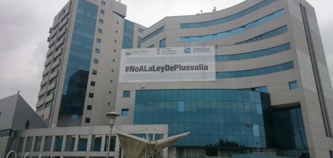 """GUAYAQUIL, Ecuador.- El edificio de las cámaras de la producción de Guayaquil amaneció con una gigantografía con un mensaje de rechazo que dice """"#NoALaLeyDePlusvalía"""". Foto: Twitter"""