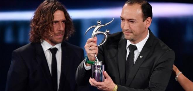 Juan Carlos de la Cuesta (d.), presidente del equipo colombiano, recibió el trofeo de las manos de Carles Puyol. Foto: AFP
