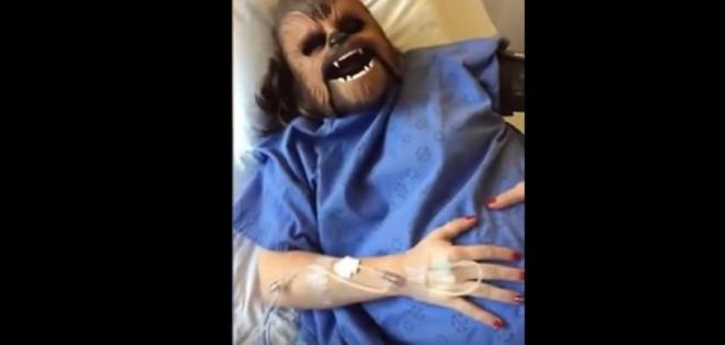 La mujer en labor de parto aparece disfrazada con la  máscara en su cama de hospital.