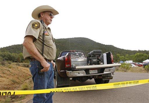 El agente del Sheriff del condado de Gila Larry Hassinger monta guardia en la entrada de la zona recreativa First Crossing durante una operación de búsqueda y rescate de víctimas de una inundación repentina causada por el río East Verde, el domingo 16 de julio de 2017, en Payson, Arizona. Foto: AP