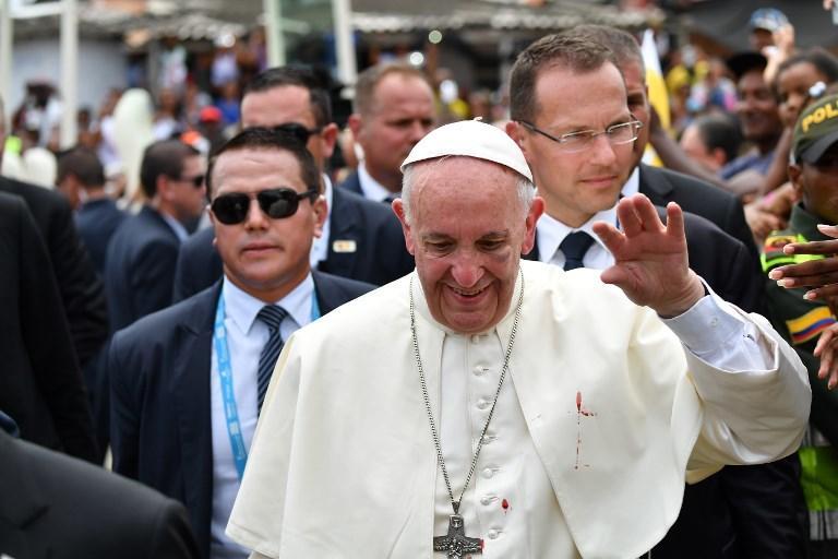 Durante su recorrido en Cartagena, Francisco se golpeó contra el vidrio del papamóvil. Fotos: AFP y AP