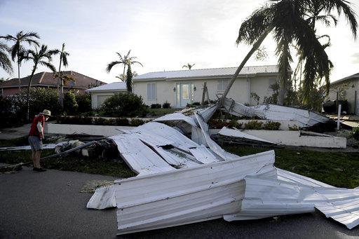 Un techo destruido es visto en el césped de una casa cuando Rick Freedman examina los daños sufridos por su vecino a causa del huracán Irma en Marco Island, Florida, el lunes, 11 de septiembre del 2017. Foto: AP