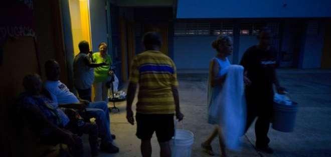 En esta fotografía del jueves 12 de octubre de 2017, personas que se quedaron sin hogar tras el paso del huracán María cargan cubos con agua para bañarse y hacer limpieza, en una escuela convertida en albergue que carece de electricidad en Toa Baja, Puerto Rico. Foto: AP