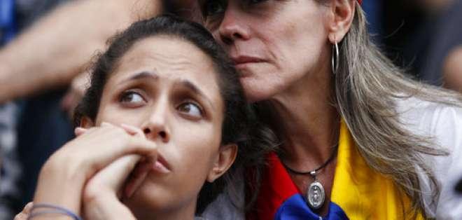 Fotografía de archivo del lunes 31 de julio de 2017 de dos manifestantes antigubernamentales mientras asisten a un acto público en Caracas en honor de los muertos en enfrentamientos entre fuerzas de seguridad y manifestantes. Foto: AP