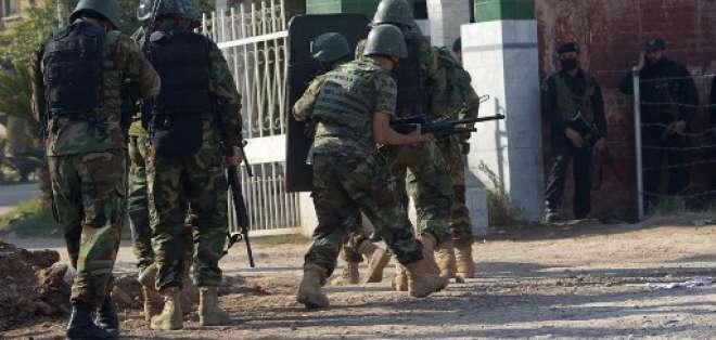 Un grupo de soldados entran a la escuela de formación agrícola, después del ataque de los talibanes. Foto: AFP
