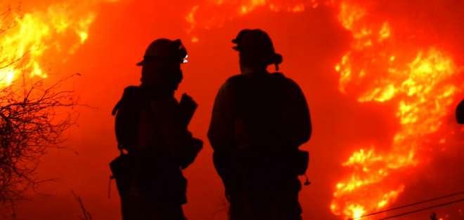 Bomberos trabajan en la protección de estructuras, mientras observan de cerca las llamas en la cima de Shepard Mesa Road, en Carpinteria, California. Foto: AP