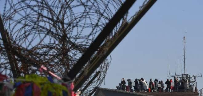 La gente mira a través de binoculares desde un mirador mientras se ve una valla militar en el parque de paz de Imjingak, cerca de la Zona Desmilitarizada (DMZ), que divide las dos Coreas en la ciudad fronteriza de Paju el 1 de enero de 2018. Foto: AFP