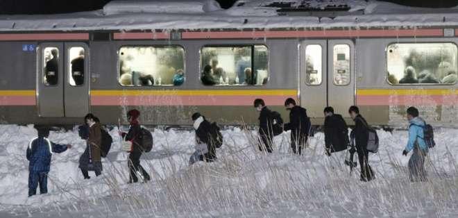 TOKYO, Japón.- 430 pasajeros del tren tuvieron que caminar por la vía debido a la nieve que cubrió gran parte de la costa occidental de Japón. Foto: AP