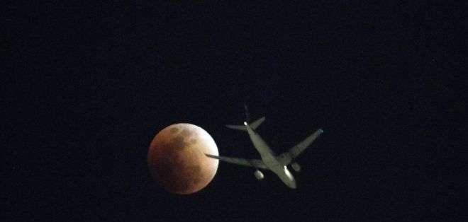Un avión pasa enfrente de la superluna vista en Hong Kong, donde se pudo ver una serie de eventos astronómicos.