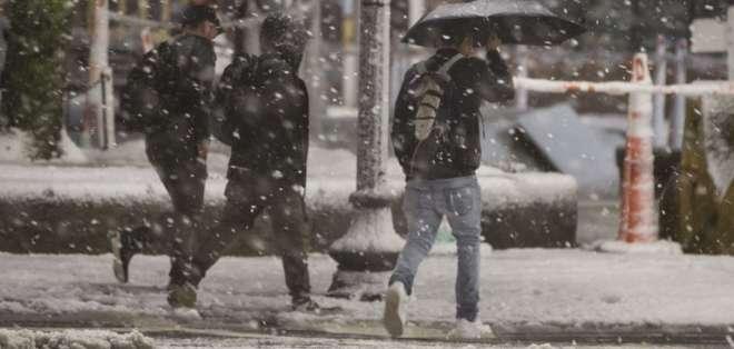 BOSTON, EE.UU.- Los peatones se protegen con abrigos y paraguas por las repentinas lluvias y nevadas. Foto: AFP