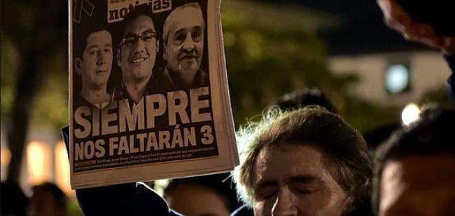 Un hombre sostiene un diario en cuya portada aparecen los periodistas asesinados. Foto: AFP.
